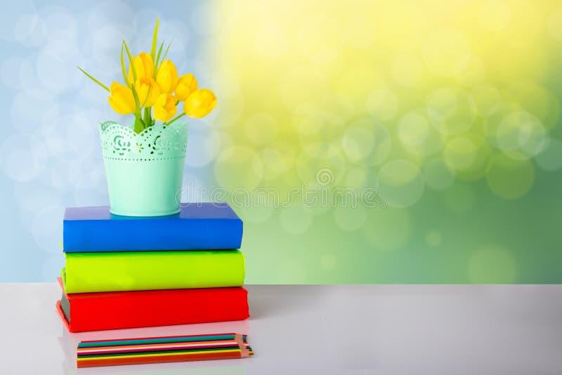 五颜六色的学校设备和黄色郁金香在桌上反对bri 免版税库存图片