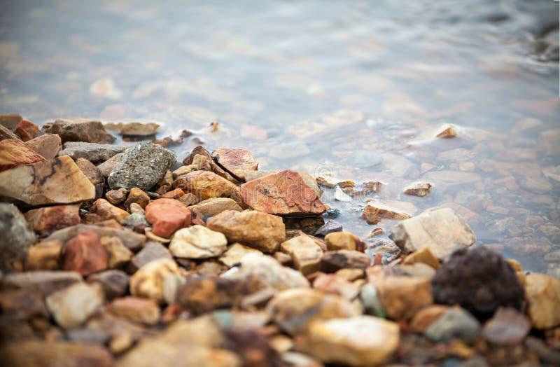 五颜六色的小卵石,与石渣的清楚的水在湖的边,背景的imafe 免版税库存图片