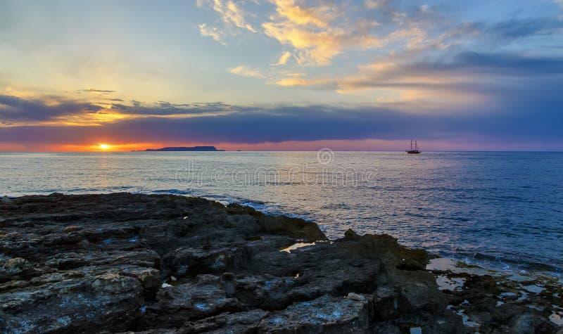 五颜六色的山剪影和古老船反对明亮的橙色太阳,掩藏在蓝色云彩后,海在 免版税库存图片