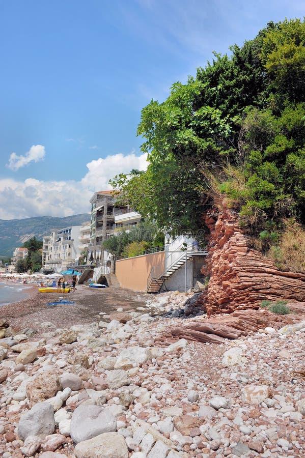 五颜六色的峭壁和用在亚得里亚海,黑山,欧洲的石头盖的海海滩 库存图片