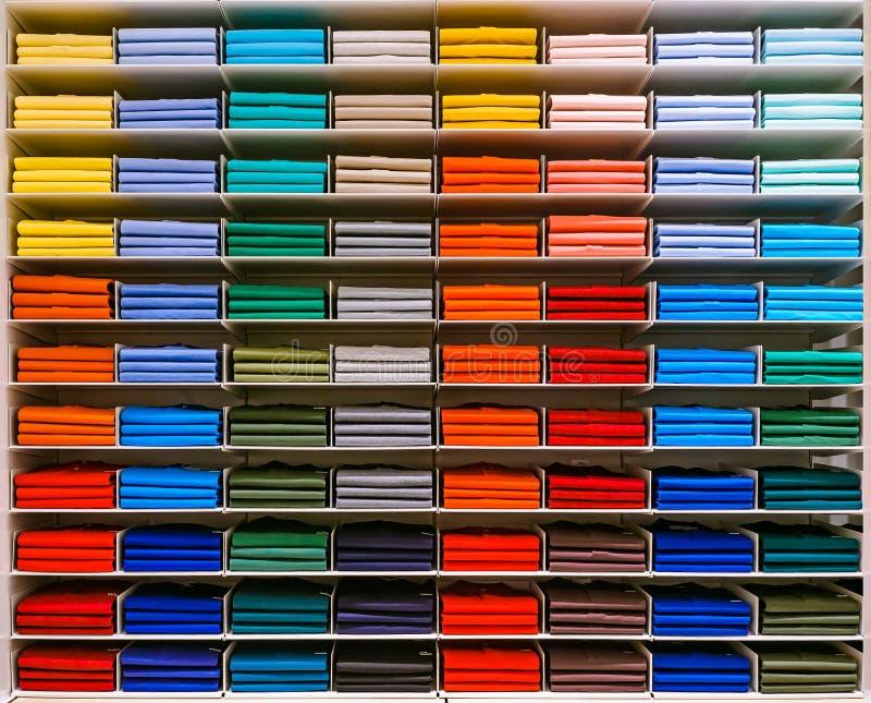 五颜六色的彩虹衣裳背景 各种各样的充满活力的颜色衬衣在一个架子完全折叠了在商店 色的男性 库存照片