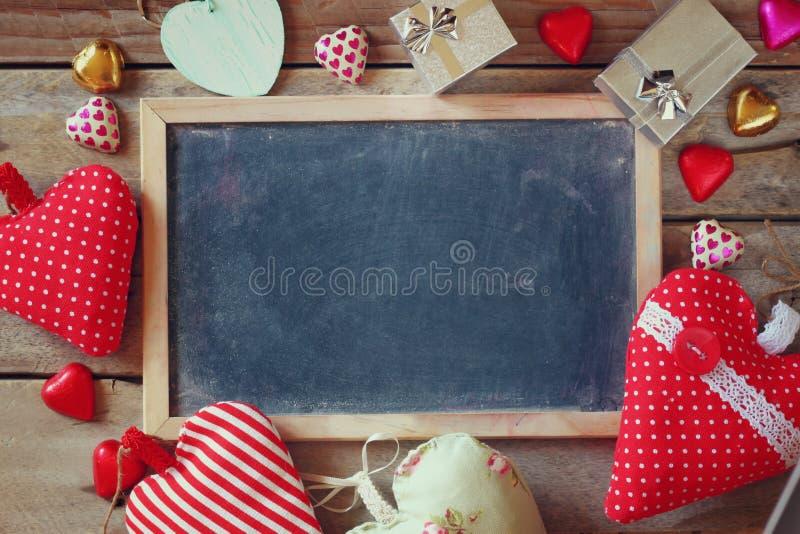 五颜六色的心脏形状巧克力、织品心脏、礼物盒和粉笔板的顶视图图象在木桌上 库存图片