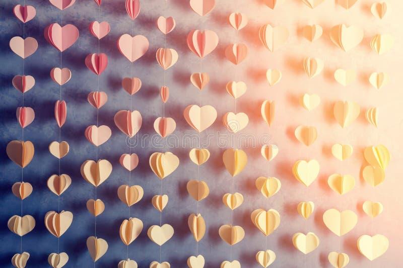 五颜六色的心脏裱糊垂悬在墙壁上的诗歌选 浪漫情人节背景 Instagram样式定了调子照片 免版税库存图片