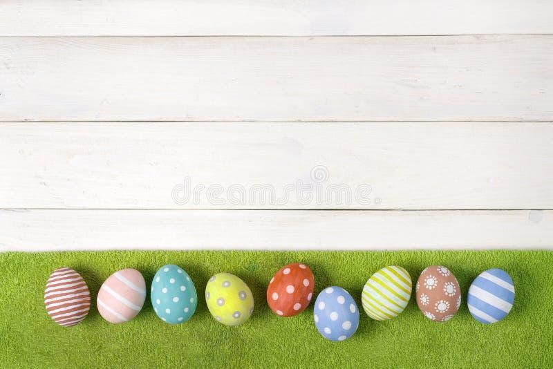 五颜六色的手工制造复活节彩蛋在白色木背景的绿色草坪说谎 平的位置样式 免版税库存照片