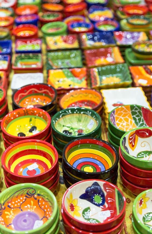 五颜六色的手画碗和罐在市场上的行安排了 库存图片