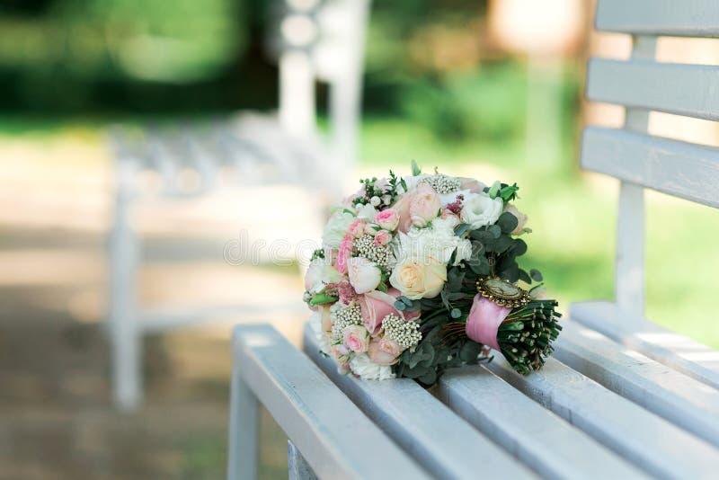 五颜六色的新娘花束在长凳说谎 衣物夫妇日愉快的葡萄酒婚礼 库存照片