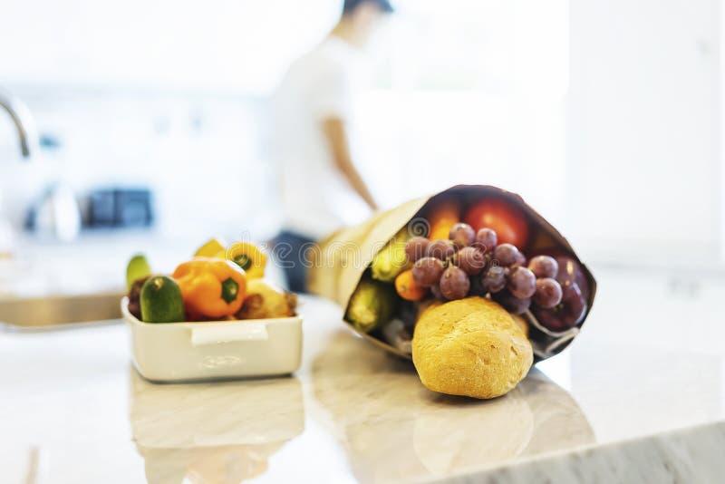 五颜六色的新鲜蔬菜和果子与袋子买菜在厨房里 库存图片