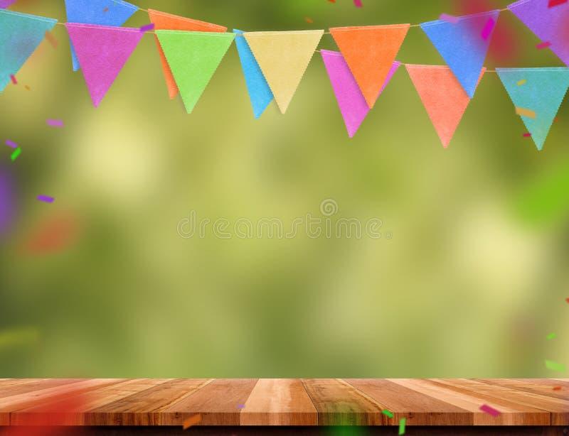 五颜六色的旗子横幅和五彩纸屑在木桌上与迷离绿化 库存照片