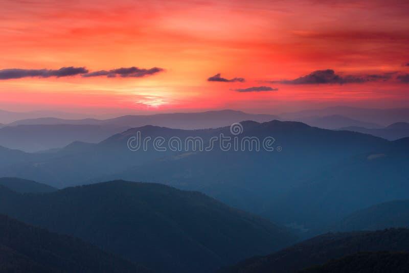 五颜六色的日落全景在山的 严重的阴暗天空 免版税库存照片