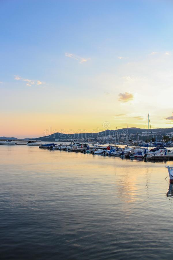 五颜六色的日落在城市戏曲,有小船的希腊港口  库存图片