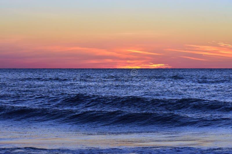 五颜六色的日落背景的蓝色海洋在克利尔沃特海滩 库存照片