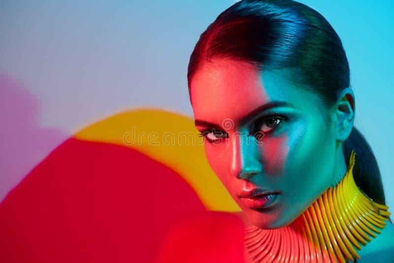 五颜六色的明亮的光的时装模特儿妇女与五颜六色明亮光摆在的时髦构成和manicureFashion式样妇女 免版税库存照片