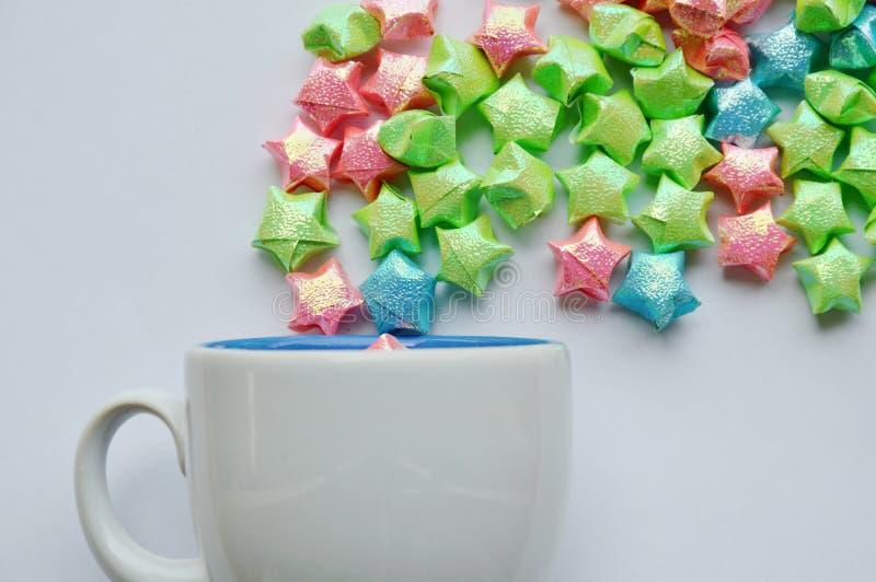 五颜六色的星纸漂浮从在白色背景的咖啡杯 库存图片