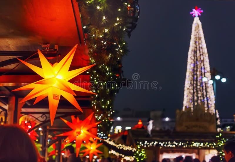 五颜六色的星Xmas树待售和光在圣诞节市场上 图库摄影