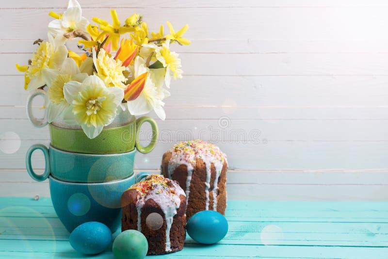 五颜六色的春天开花,复活节蛋糕和鸡蛋在木背景 免版税库存图片