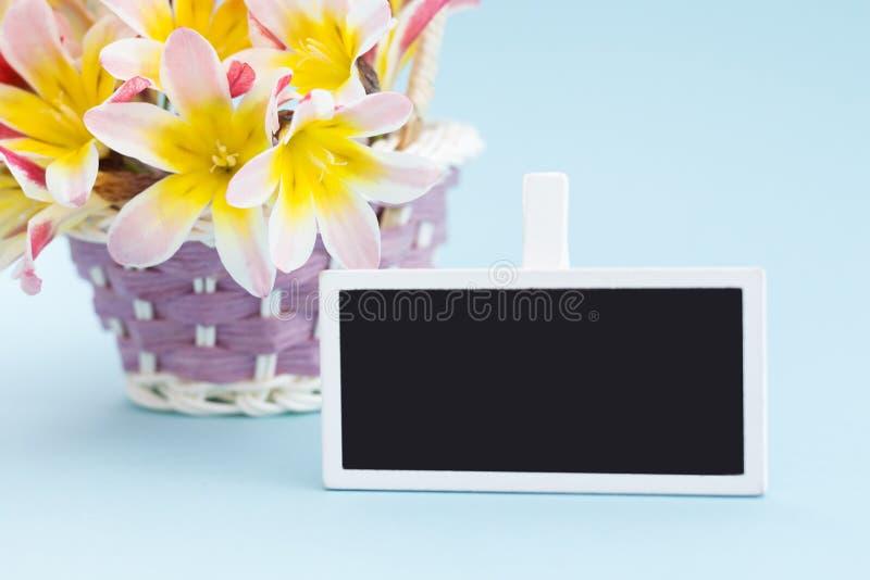 五颜六色的春天花花束,在柳条筐和空白的黑板标志文本的 库存照片