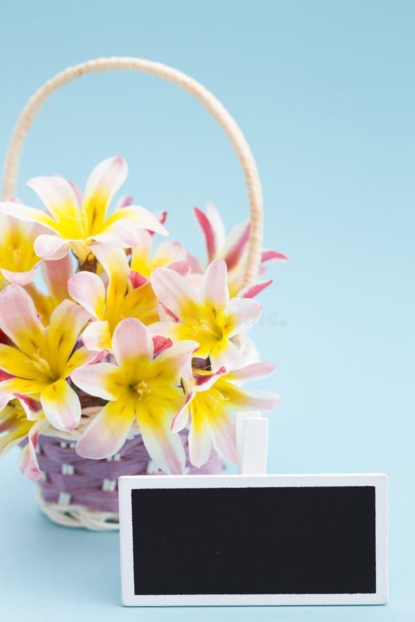 五颜六色的春天花花束,在柳条筐和空白的黑板标志文本的 库存图片
