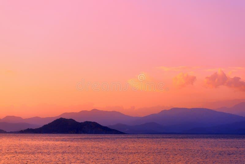 五颜六色的暮色海景 云彩和山在天际 库存图片