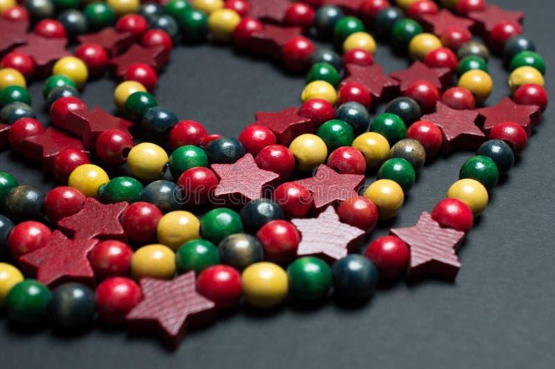 五颜六色的木圣诞节装饰小珠在中立表面上的一个螺旋安排了 免版税库存图片