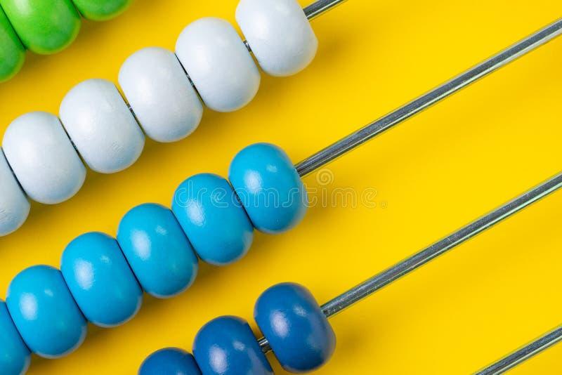 五颜六色的木算盘在黄色背景,企业fina成串珠状 图库摄影