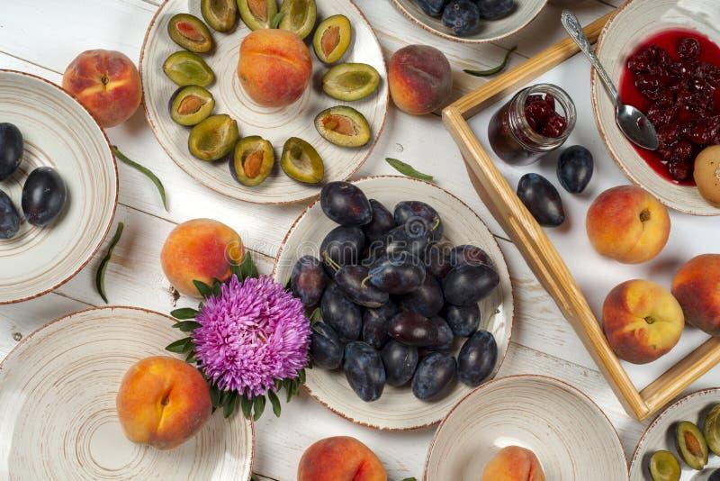 五颜六色的果子套在碗的紫色,红色和橙色背景 李子,桃子,在白色桌面上切的西瓜 免版税库存图片