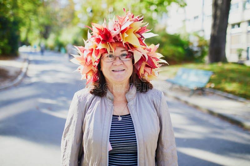 五颜六色的枫叶的愉快的中间年迈的妇女缠绕 免版税图库摄影