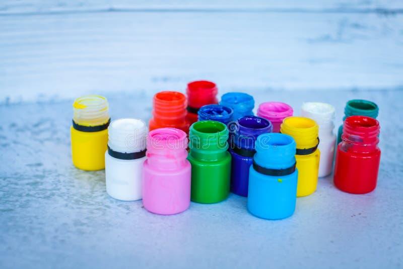 五颜六色的树胶水彩画颜料或丙烯酸漆在瓶子在白色难看的东西背景,选择聚焦 免版税库存图片