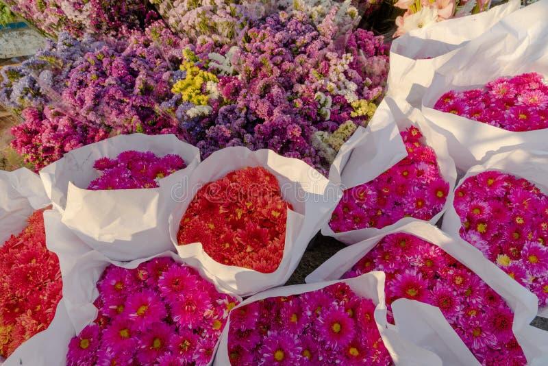 五颜六色的桃红色和红色菊花在白皮书和其他冬天花包裹的花花束 免版税库存照片