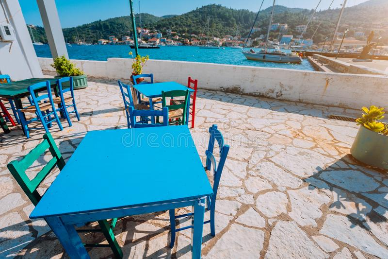 五颜六色的桌和椅子在晴朗的大阳台 由海的传统乡下小酒馆 热的希腊渔村 免版税库存图片