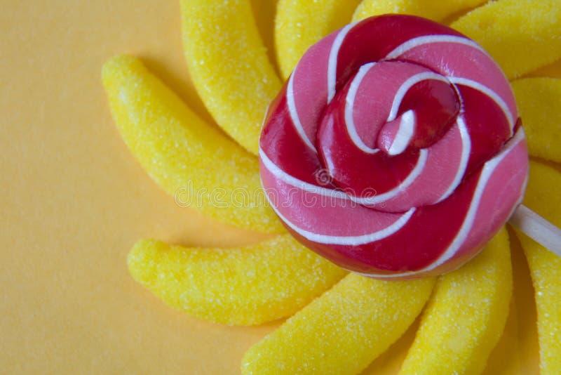 五颜六色的棒棒糖和不同被上色围绕糖果 顶视图 免版税库存图片