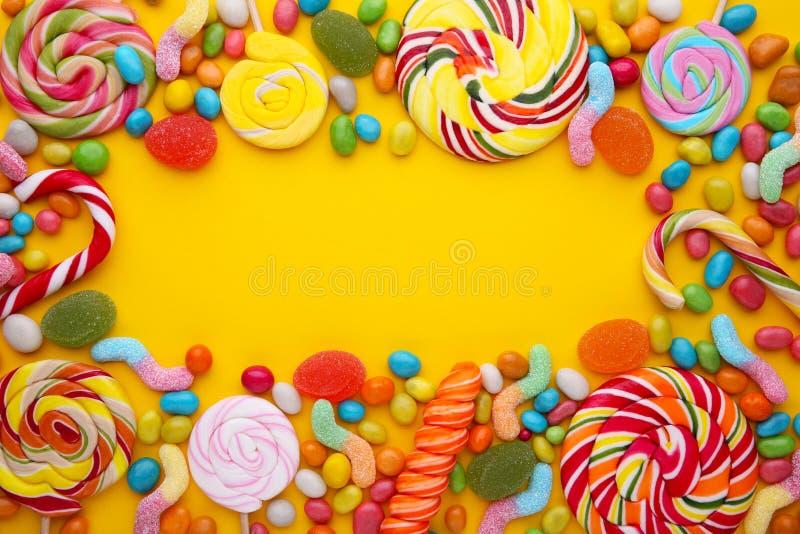 五颜六色的棒棒糖和另外色的圆的糖果在黄色背景 免版税图库摄影