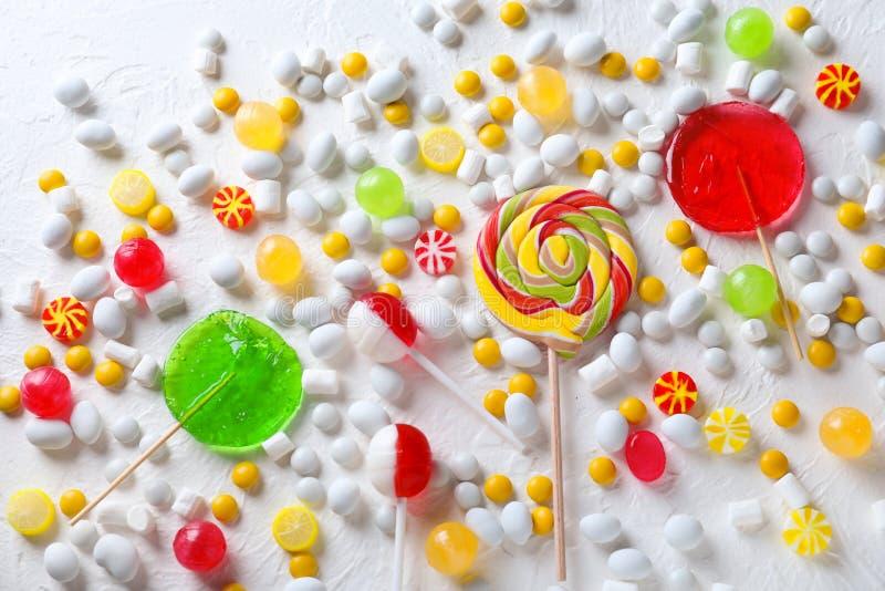 五颜六色的棒棒糖用在轻的织地不很细背景的蛋白软糖 库存照片
