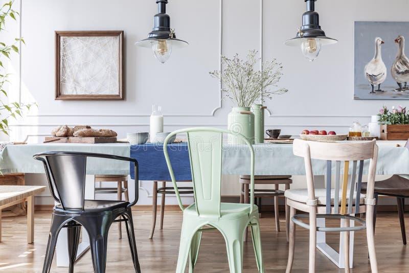 五颜六色的椅子在折衷灰色餐厅内部的桌上与灯和花 实际照片 库存照片