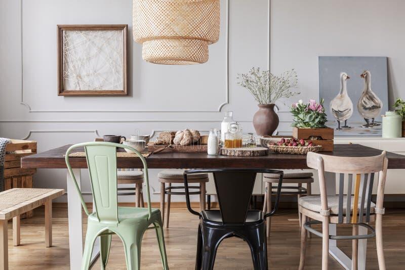 五颜六色的椅子在灰色餐厅内部的木桌上与海报和花 实际照片 库存图片