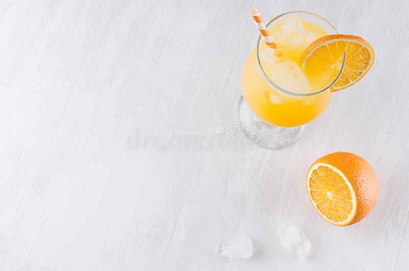 五颜六色的橙色凉快的柑橘鸡尾酒用切片桔子,冰块,在白色现代木背景,顶视图的秸杆 图库摄影
