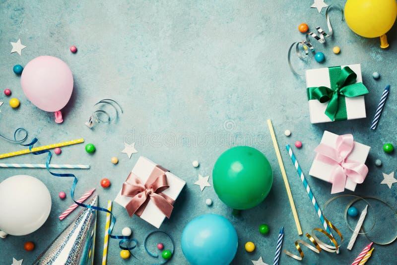 五颜六色的气球、礼物或者礼物盒、五彩纸屑、糖果和飘带在葡萄酒绿松石台式视图 生日背景 库存图片