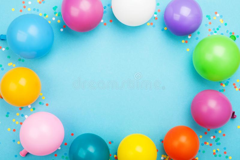 五颜六色的气球和五彩纸屑生日框架在蓝色台式视图 平的位置样式 库存照片