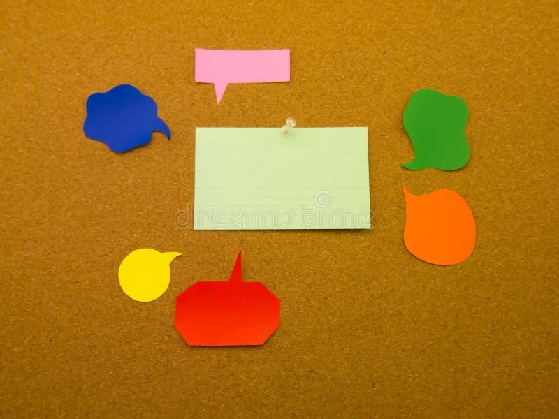 五颜六色的气球和笔记(黄柏板背景) 图库摄影