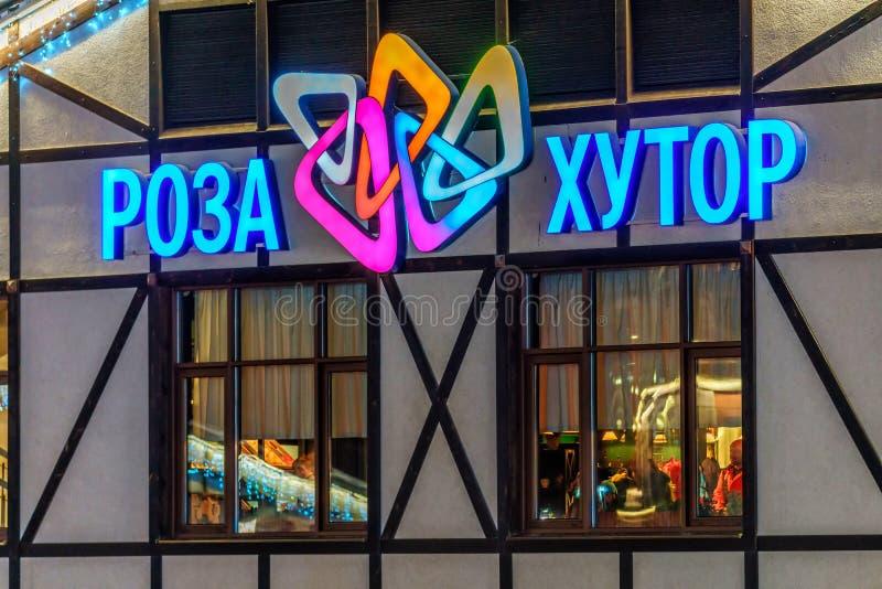 五颜六色的氖阐明了罗莎Khutor滑雪在修造的外部的山区度假村标志 罗莎Khutor商标背景 库存照片