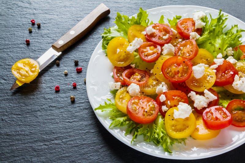 五颜六色的沙拉、新鲜的绿色叶子和切的红色和黄色西红柿,白色板材,刀子,黑石背景 免版税库存照片
