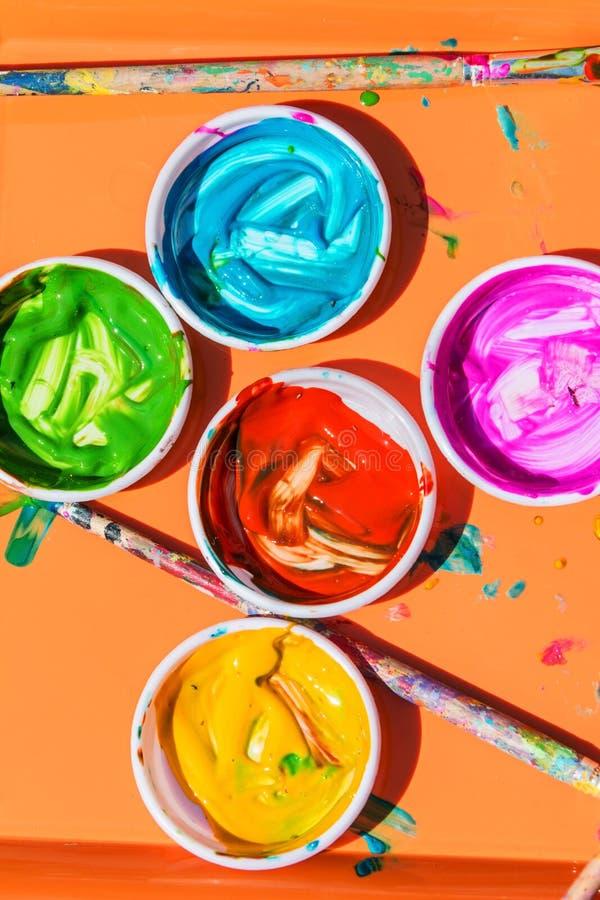五颜六色的油漆在孩子的碗坐能绘与 免版税库存照片