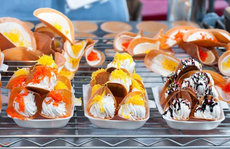 五颜六色的泰国传统甜快餐和点心、充满甜椰子奶油和被盐溶的泰国酥脆薄煎饼或者泰国绉纱 免版税库存图片