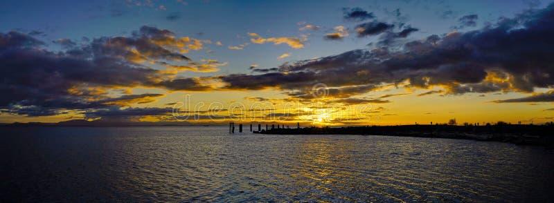 五颜六色的海洋海滩日落,新月形海滩全景  免版税库存照片