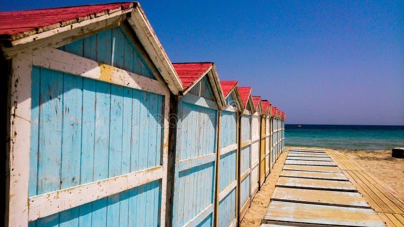 五颜六色的海滩客舱行在海附近的 库存照片
