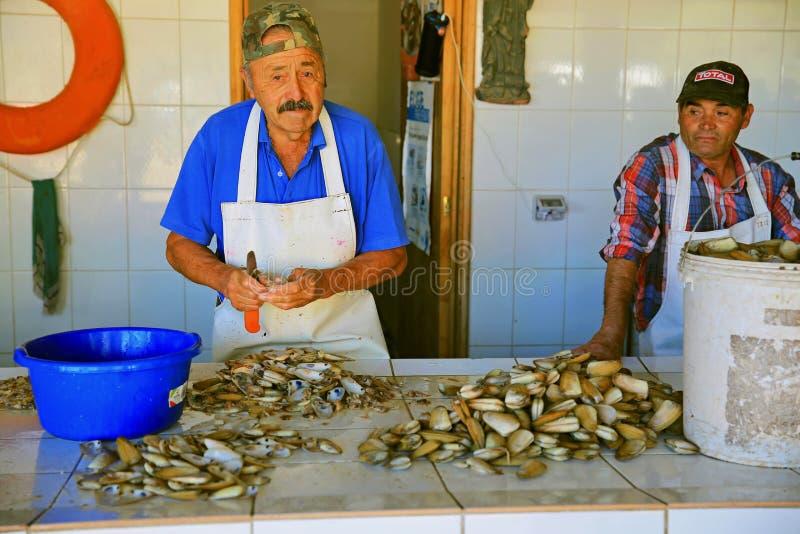 五颜六色的渔夫在智利鱼市上去外皮淡菜 免版税库存照片