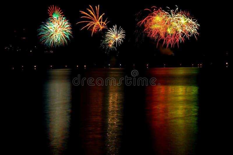 五颜六色的烟花在晚上,反映在湖 免版税库存图片