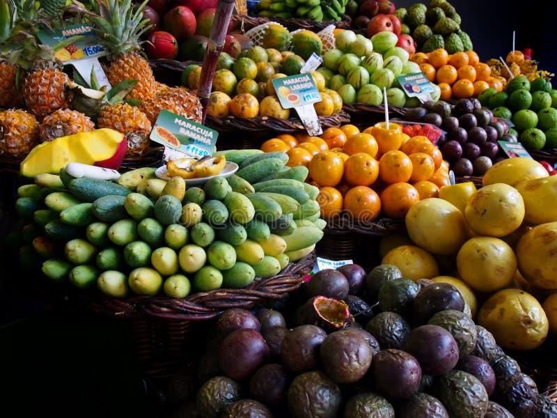 五颜六色的热带水果显示在销售中的在丰沙尔马德拉标志的市场摊位读了森林李子西红柿橙色passionfruit 库存图片