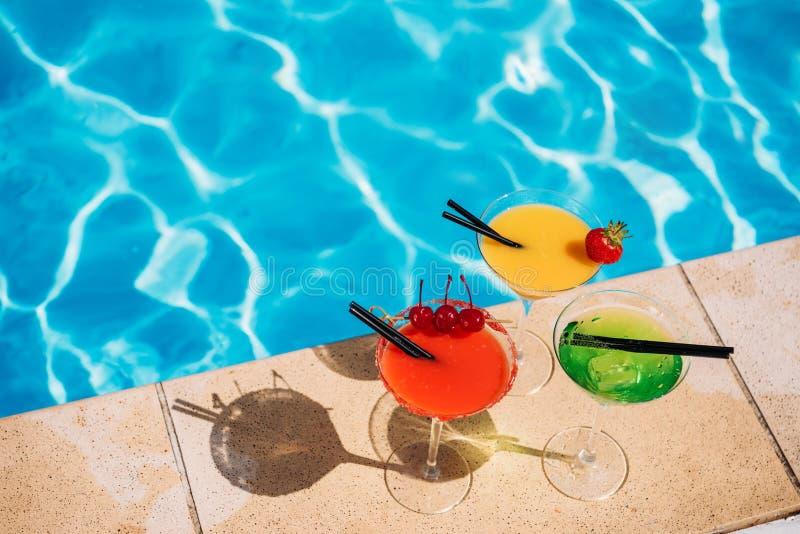 五颜六色的热带鸡尾酒用在游泳池边缘的莓果  免版税库存照片