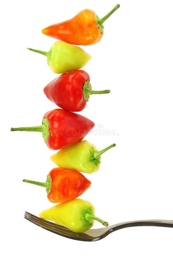 五颜六色的热的微型辣椒在叉子平衡 免版税库存图片