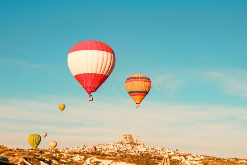 五颜六色的热空气迅速增加飞行靠近Uchisar城堡在日出,卡帕多细亚,土耳其 免版税库存图片